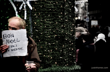 "An elderly man holding a cardboard written in French: ""Merry Christmas, Thank you for the kind gesture"""