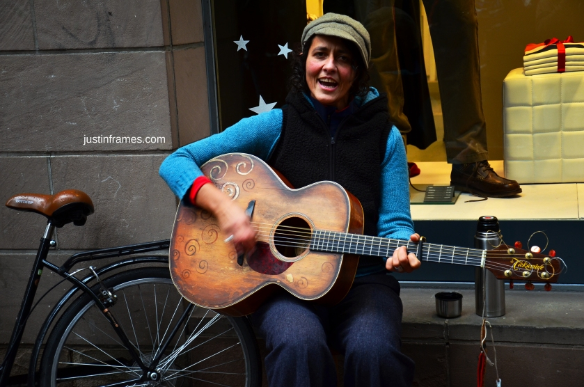 A street musician entertaining passersby in a street in Strasbourg.