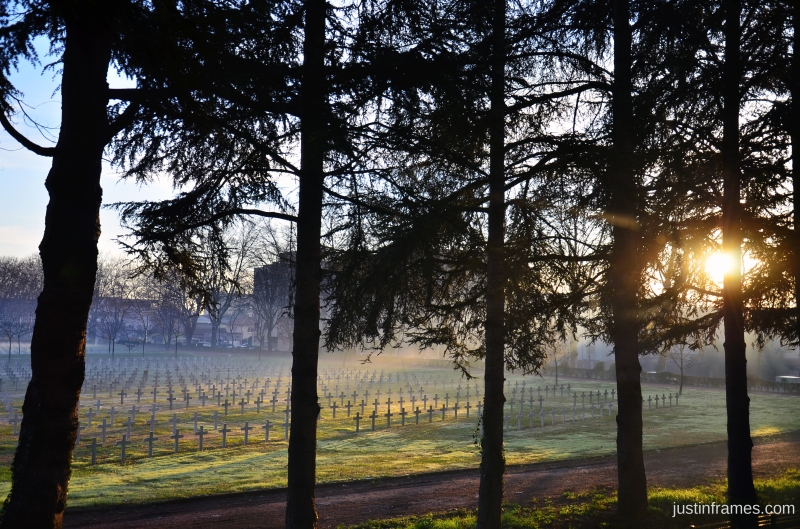 World war two cemetery bathed in the morning rays of winter, partially shrouded in fog.